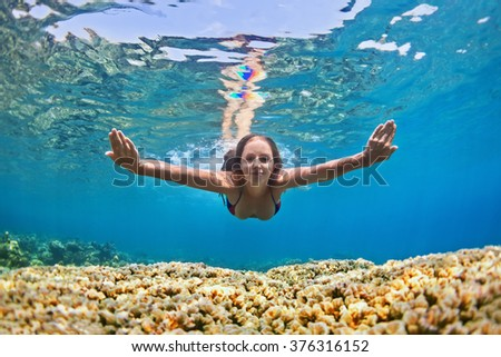 Happy beautiful girl - young woman dive underwater with fun over coral reef in sea pool. Healthy active lifestyle, people water sport outdoor activity and swimming lessons on beach summer holidays. - stock photo