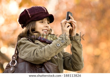 happy beautiful little girl take a photograph on mobile phone, autumnal portrait - stock photo