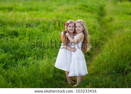 Happy beautiful  little girls in white dresses having fun on the meadow - stock photo