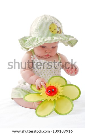 Happy beautiful 6 month old baby girl in green seersucker sun hat and sun dress sits and plays with a big yellow toy daisy. Pastels, isolated on white background, vertical, copy space. - stock photo