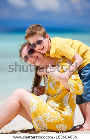 Happy beautiful mother and son enjoying beach time