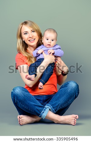 Happy beautiful mother embracing her adorable baby. Family concept. Studio shot. - stock photo