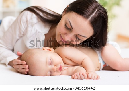 happy beautiful mother looking at sleeping baby - stock photo