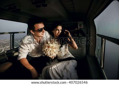 Happy beautiful newlyweds in the helicopter - stock photo