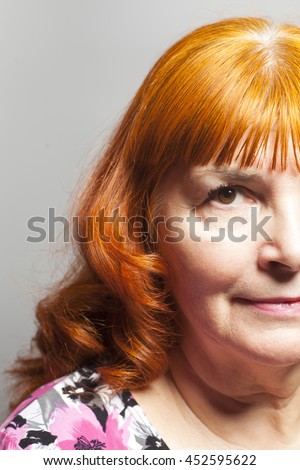 Happy beautiful older lady posing on gray background