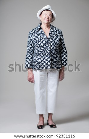 Happy beautiful older lady posing on gray background. - stock photo