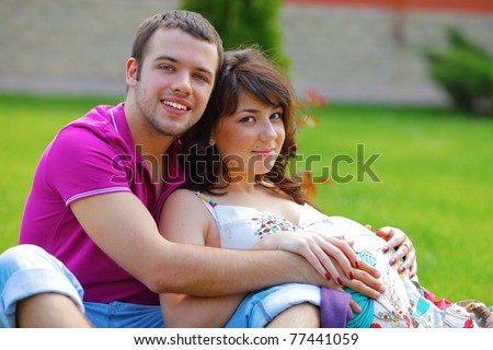 Happy beautiful pregnant woman with his husband sitting on the lawn outside - stock photo