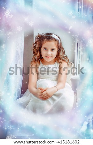Happy beautiful Princess girl in a white dress smiling. Happy New Year little Princess