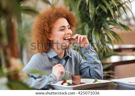 Happy beautiful redhead young woman sitting in cafe and eating chocolate dessert - stock photo