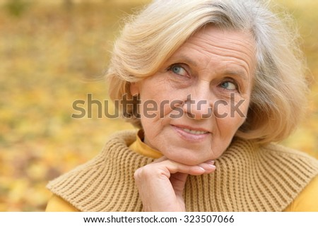 Happy beautiful senior woman in the autumn park