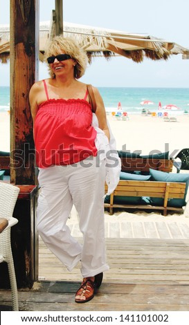 Happy beautiful senior woman on summer vacation at sea - stock photo