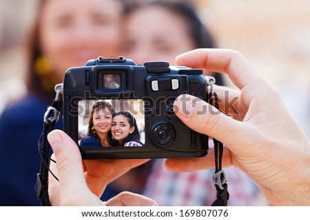 Happy beautiful smiley girlfriends being photographed by a man. - stock photo
