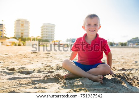 Happy beautiful smiling child sitting at the sand beach, looking