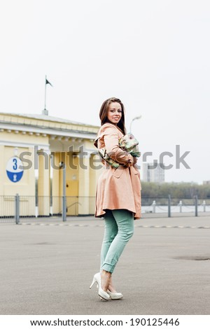 Happy beautiful smiling woman in fashion outfit on urban background - stock photo