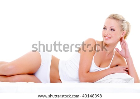 Happy beautiful smiling woman with a sexy body  lying in underwear on the white bed - stock photo