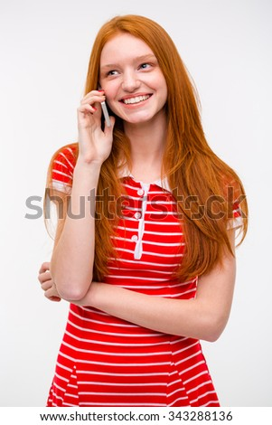 Happy beautiful smiling young woman with long red hair in red striped dress talking on cellphone - stock photo