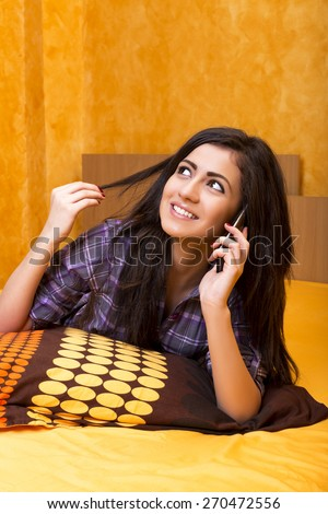 Happy beautiful teenage girl speaking on her smart phone on the bed  - stock photo