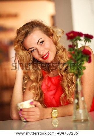Happy beautiful woman at home at a table with a cup of coffee