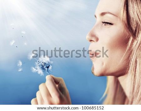 Happy beautiful woman blowing dandelion over sky background, having fun and playing outdoor, teen girl enjoying nature, summer vacation and holidays, young pretty female holding flower, wish concept - stock photo