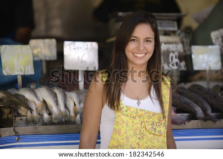 Happy beautiful woman buying fish at a fish shop street market. - stock photo