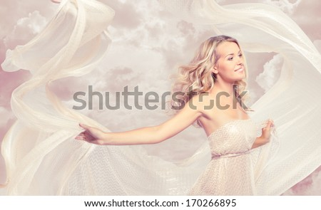 Happy beautiful woman carefree dancing with flying fabric