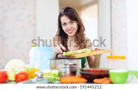 Happy beautiful woman cooking vegetarian salad in  kitchen  at home