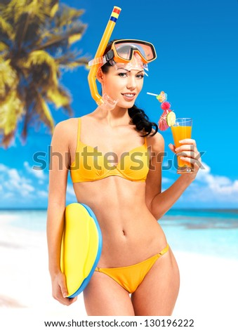 Happy beautiful woman enjoying at beach. Pretty girl with a protective swim mask on the head. - stock photo