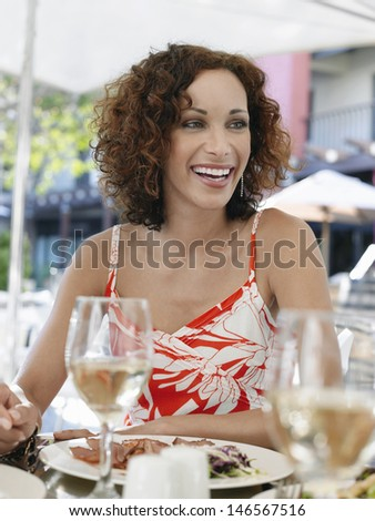 Happy beautiful woman enjoying meal at outdoor cafe - stock photo