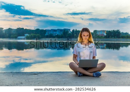 happy beautiful woman, girl with laptop surfing the web near by lake - stock photo
