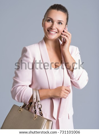 Happy beautiful woman holds handbag and mobile over white background. Attractive young girl in casual clothing