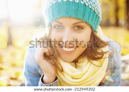 Happy beautiful woman in autumnal park