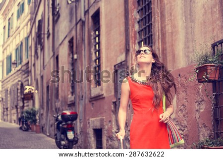 Happy beautiful woman in red summer dress walking joyful and cheerful smiling in Rome, Italy. Pretty sexy fashion model girl in her 20s. Female model outside. - stock photo