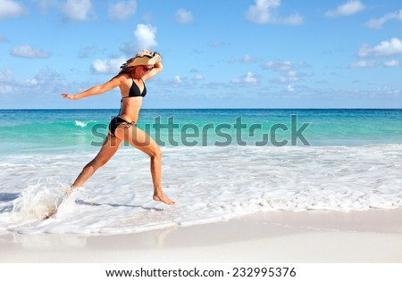 Happy beautiful woman running on the beach. Caribbean vacation - stock photo