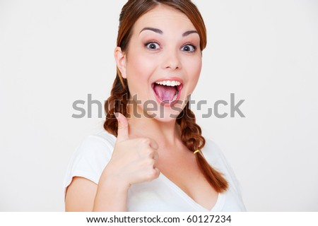 happy beautiful woman showing thumbs up over grey background - stock photo