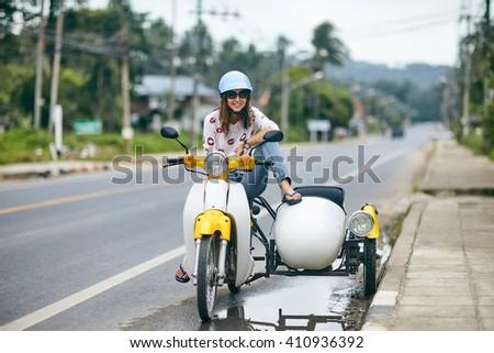 Happy beautiful woman sitting on a retro motorbike - stock photo