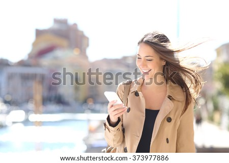 Happy beautiful woman walking and writing or reading sms messages on line on a smart phone while the wind moves her hair in a street of a port - stock photo