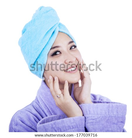 Happy beautiful woman wearing a towel isolated on white background