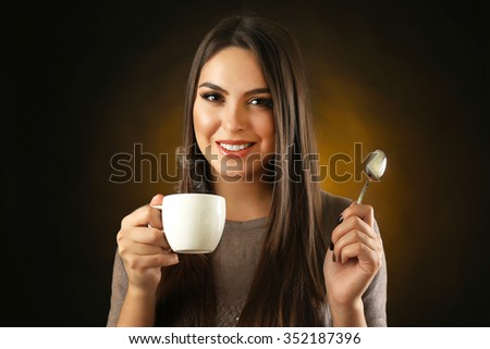 Happy beautiful woman with cup of coffee and spoon on dark background - stock photo
