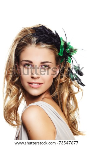 happy beautiful woman with long blond hair in big hairstyle, wearing flower headband with green and black feathers on white background - stock photo
