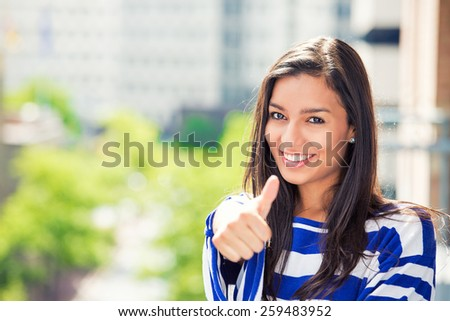 Happy beautiful woman with thumbs up isolated on city background. Positive face expression life perception  - stock photo