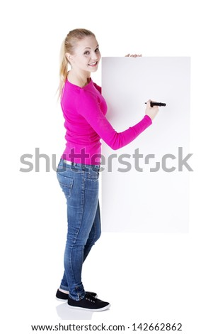 Happy beautiful woman writing with a marker on blank board. Student or businesswoman. - stock photo