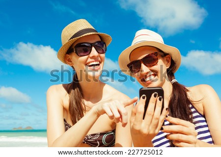 Happy beautiful women using mobile smart phone at the beach - stock photo