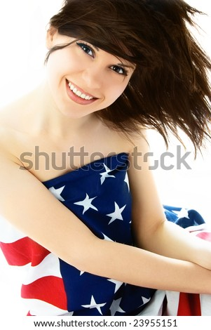happy beautiful young brunette woman wrapped into an American flag - stock photo