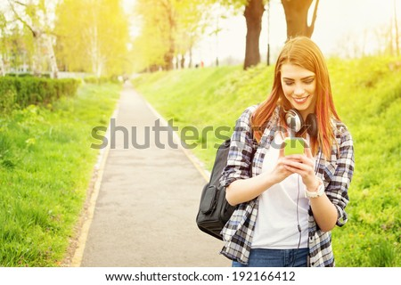 Happy beautiful young Caucasian redhead high school girl with green smart phone outdoors on sunny summer day texting and smiling.  - stock photo