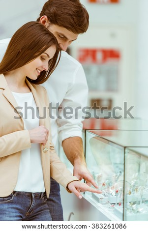 Happy beautiful young couple choosing a wedding rings and smiling while doing shopping in mall - stock photo