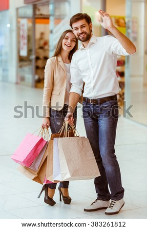 Happy beautiful young couple holding shopping bags, hugging and waving while standing in mall - stock photo