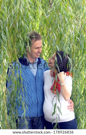 Happy beautiful young couple in the spring park. Pregnant young woman and her husband  - stock photo