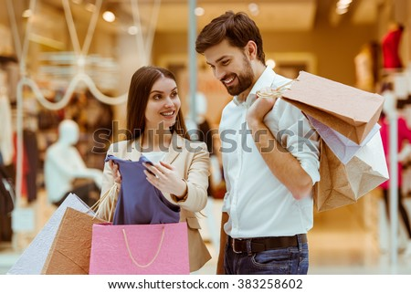 Happy beautiful young couple looking upon their purchase and smiling while standing in mall - stock photo