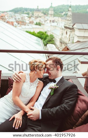 happy beautiful young couple sitting on couch - stock photo