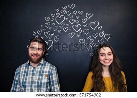 Happy beautiful young couple smiling and standing over background of chalkboard with drawn hearts  - stock photo